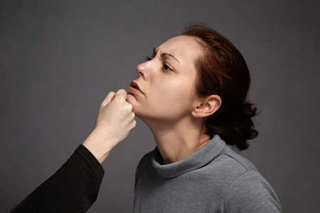 A woman's fist strikes the woman's chin. Problems of mutual understanding, conflict and psychology. Domestic violence.
