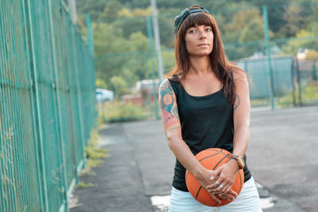 Beautiful young woman with tattoos, in a cap posing with a basketball.