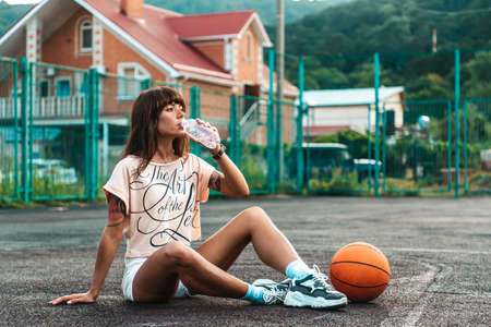 Beautiful young woman with tattoos with a basketball in her feet, drinking water from a bottle and posing for the camera. 版權商用圖片