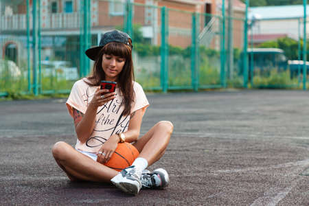 A beautiful young woman with tattoos, wearing a cap, sitting on a sports court with a basketball and looking into a mobile phone. Copy space.