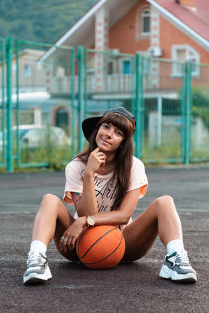 Beautiful young woman with tattoos, wearing a cap, sitting on the sport court with a basketball.