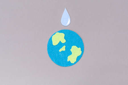 World Water Day. Carved out of felt is the symbol of the planet Earth and a drop of water. Gray background. Copy space. Environmental protection concept. 版權商用圖片
