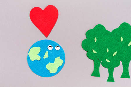Cuted out of felt the lovely planet Earth with trees and heart. Gray background. Flat lay. The concept of Planting trees and Earth Day.