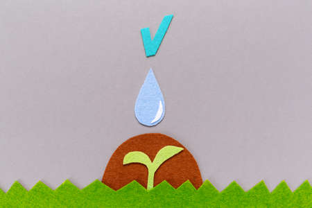 Earth Day. Cutted out of felt drop and soil with plant sprout. Gray background. Copy space. The concept of environmental protection and planting trees. 版權商用圖片