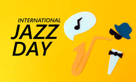 Silhouette of a musician with a saxophone from which melodie flew out, on a yellow background, cutted out of felt. Flat lay. International Jazz Day. 版權商用圖片