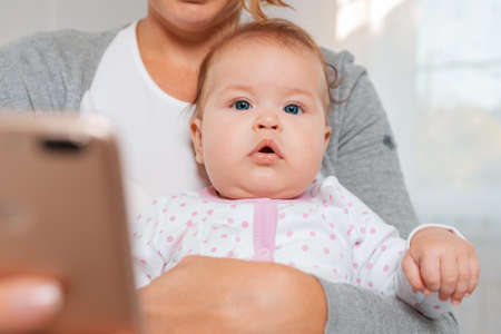 Close-up portrait of a baby sitting in the arms of a mother who uses a smartphone. Bottom view.