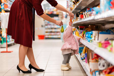 A young mother gives her baby, standing at the shelf in the supermarket, a pear and a candy. Close up. The concept of family shopping.