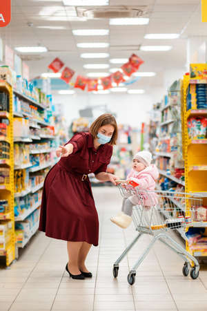 New normal. A young mother with a medical mask on her face shows something with her hand to her baby sitting in a grocery cart. The concept of shopping during the coronavirus pandemic.