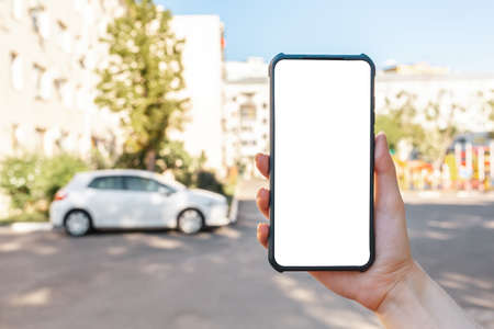 A woman holds a cellphone with mock up, hand close-up. In the background is a city street with car. The concept of online navigation and modern technologies. 版權商用圖片