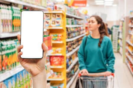 A person's hand holds a mobile phone, with a shopping basket on the screen. In the background, a woman is pushing a grocery cart in a supermarket. Mock up. The concept of online shopping. 版權商用圖片