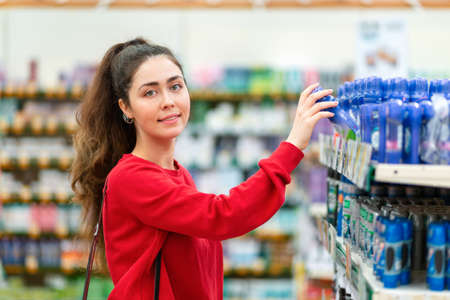 A young smiling woman taking a bottle of cosmetics from the shelf. The concept of buying cosmetic products.