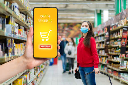 Shopping. A young woman in a medical mask on her face posing in the supermarket. The hand holds the smartphone on the left. The concept of online shopping and the new normal.