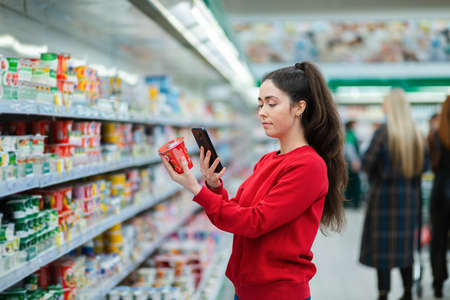 A young woman scans the QR code on a package of yogurt. In the background, a supermarket with visitors in a blur. The concept of modern technologies.