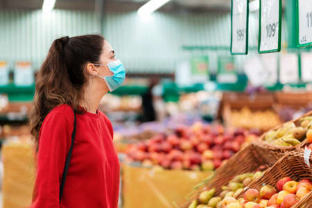 Shopping. Portrait of a young woman in a medical mask on her face looking at apples in a supermarket. The concept of shopping and the new reality.
