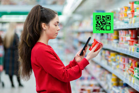 A young woman scans the QR code on a package of yogurt. A picture with a code is displayed above the product. Side view. The concept of consumption and modern technologies.