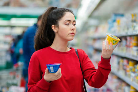 Shopping. Portrait of a young pretty woman chooses between two yogurts. The concept of consumerism and choice.