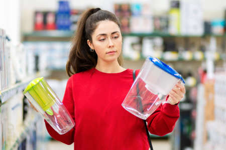 Portrait of young woman chooses between two carafe with a water filter in a home appliance store. The concept of consumerism. 版權商用圖片