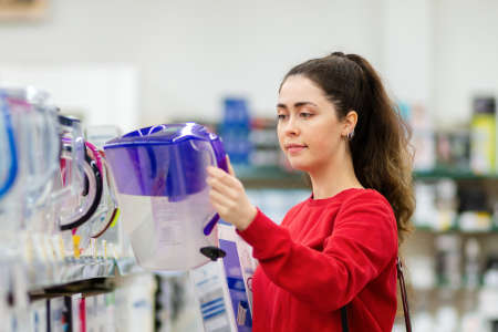 Portrait of a young caucasian woman chooses purple carafe with a water filter in a home appliance store. Concept of home appliances.