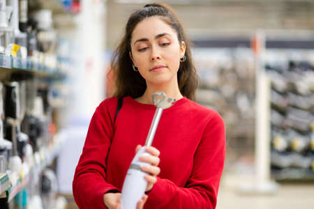 A young woman chooses a blender in a home appliance store. Side view. The concept of consumerism and shopping.