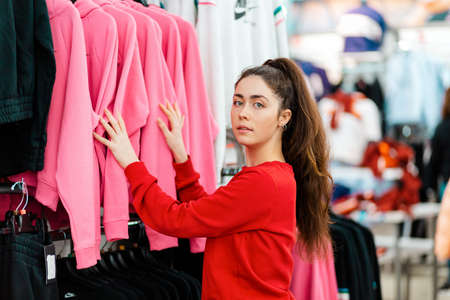 A young beautiful Caucasian woman choosing clothes in a store. Side view. The concept of shopping and consumerism. 版權商用圖片 - 167284478