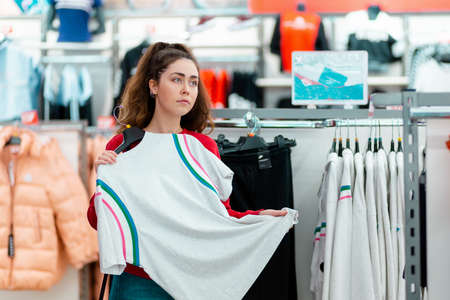 Portrait of a young pensive woman choosing white t-shirt in a store. The concept of shopping and consumerism.