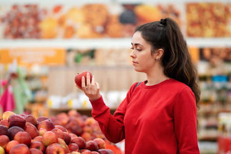 Shopping. Portrait of a young Caucasian woman choosing apples in a supermarket. The concept of shopping and consumerism. 版權商用圖片