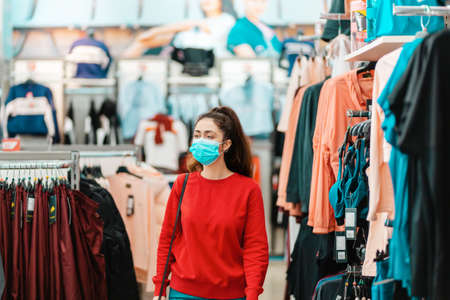 Antiviral protection in public places. Portrait of young pretty woman in a medical mask choosing clothes in a store. The concept of shopping during a viral pandemic.