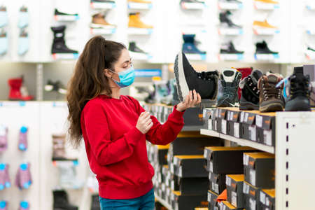 Consumerism. Portrait of young caucasian woman in a medical mask chooses shoes in a store. Side view. The concept of shopping during a viral pandemic.