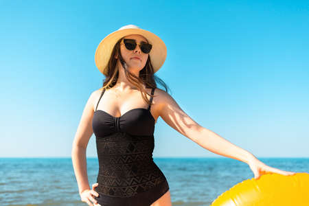 A young woman in a black swimsuit and hat holds an orange swimming circle with her hand and looking at the distance. In the background sea and sky.The concept of holiday resort and travel. Bottom view and copy space.