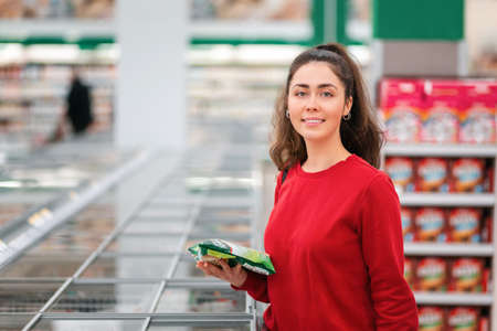 Portrait of a young smiling woman choosing frozen food, near the refrigerators. The concept of grocery shopping.