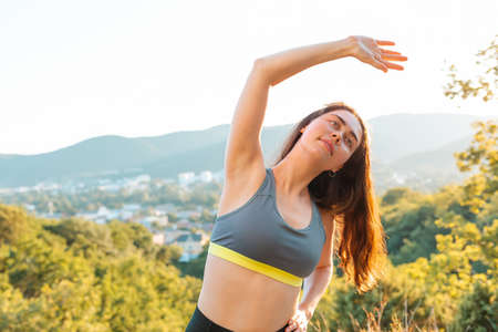 Young brunette woman warming up during a workout in the Park. The concept of yoga, sports and meditation. In the background view of the settlement and the mountains. Close up.