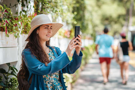 A happy woman in a hat takes photos and makes a video call via smartphone. Park street in the background. Concept of communication and social networks.