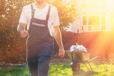 close-up of a man in a blue uniform at sunset, in motion, the gardener finished the work .cart with bags and rake in the background. Banque d'images