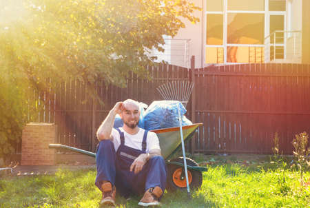 The gardener sits on the grass, leaning on a cart with tools. Sunshine from the right side. Sun glare.