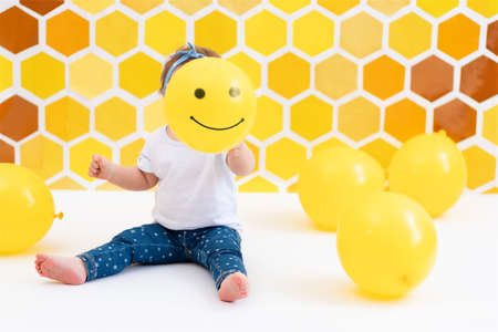 A toddler girl is sitting on a white floor with yellow balloons., Holding smiling baloon near the face. In the background is yellow honeycombs. The concept of the World Children's Day.