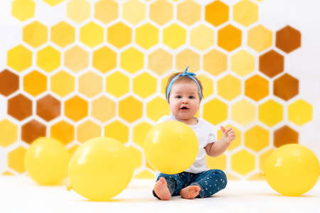 A happy toddler girl is sitting on a white floor with yellow balloons. In the background is yellow honeycombs. Copy space. The concept of the World Children's Day.