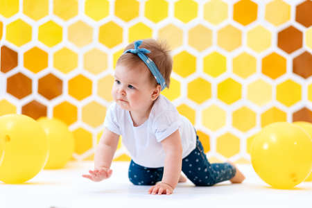Celebrating. A cute toddler girl crawling on a white floor with yellow balloons. In the background is yellow honeycombs. World Children's Day.