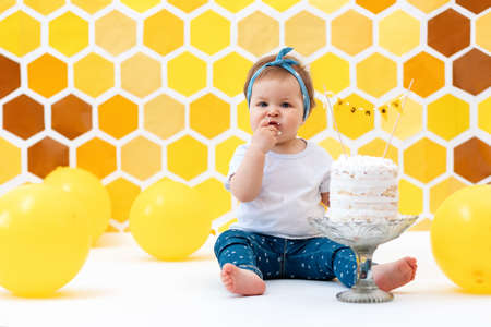 First birthday. A little female toddler sits next to a cake and eats a piece with her hands. In the background, a design of yellow honeycombs and balloons.