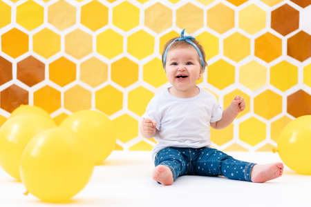 World Children's Day. A smiling toddler girl is sitting on a white floor with yellow balloons. In the background is yellow honeycombs.