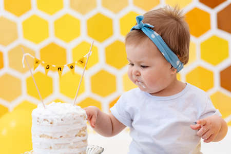 Portrait of cute baby girl sits next to a cake and eats a piece with her hands. In the background, a design of yellow honeycombs and balloons. Smash cake concept. Imagens