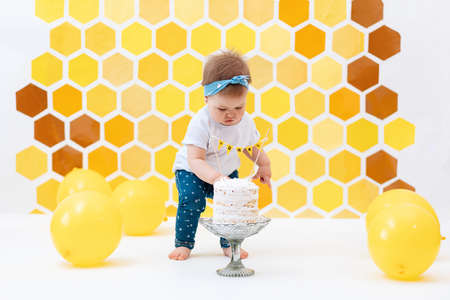 A cute little girl stands next to the cake and pokes at it with her finger. In the background is a pattern of yellow honeycombs and balloons. Smash cake concept.