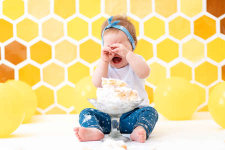 Birthday. A crying dirty toddler girl is sitting next to a broken cake. In the background is a pattern of yellow honeycombs and balloons. Smash cake concept.