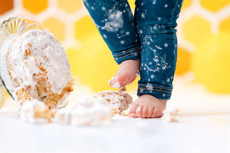 Birthday. A small child's feet smeared in cream, and a cake lying on the floor in close-up. In the background is a pattern of yellow honeycombs and balloons. Smash cake concept.
