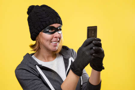 The concept of cybercrime and hacking. Portrait of a woman in a black hat, gloves and mask, who holds a mobile phone and smiles ominously. Yellow background. Copy space. Imagens