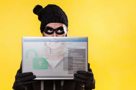 The concept of cybercrime and hacking. Portrait of a woman in a black hat, gloves and mask, who is holding a transparent tablet with a password window. Yellow background. Copy space.