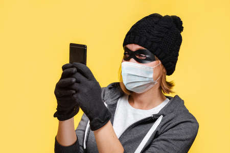 A female hacker in a black hat, gloves and a protective mask holds a smartphone in her hands, trying to hack it. Yellow background. The concept of cybercrime and new normal. Imagens