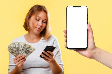 A young woman holds a fan of dollars and a cellphone. On the right is a smartphone with a white screen. Mock up. Yellow background. Online Shopping concept.