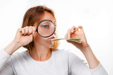 Portrait of a considerate woman looking through a magnifying glass at a small wad of dollars. White background. The concept of small salaries.