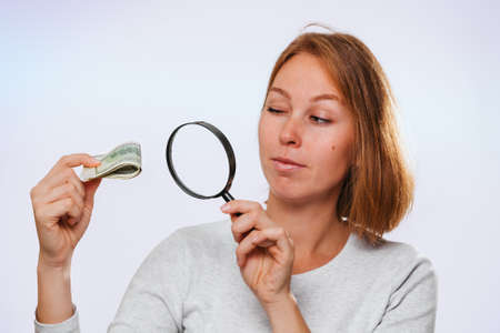 A thoughtful woman looks through a magnifying glass at a small wad of dollars. Lilac background. The concept of finance. Imagens