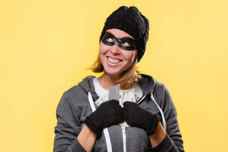 A female hacker in a black hat and a mask-glasses, greedily holds a wad of money in her hands and smiles. Yellow background. The concept of crime and theft. Imagens